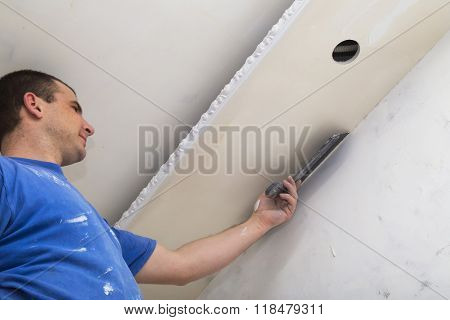 Man worker applying the layer of putty with trowel