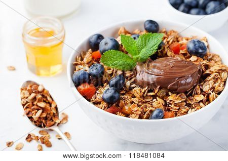 Healthy breakfast Fresh granola, muesli in bowl with milk, berries, chocolate hazelnut spread Copy s