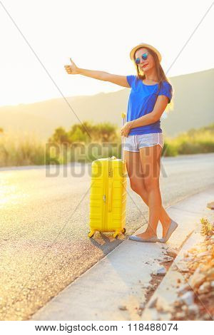 Young Woman With A Yellow Suitcase Is Traveling On The Road Hitchhiking