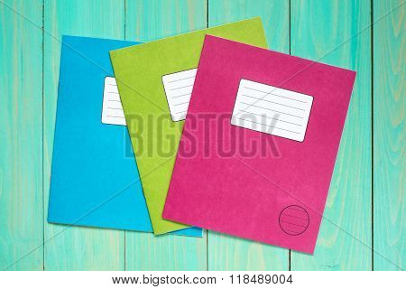 Exercise Books On The Blue Wooden Background