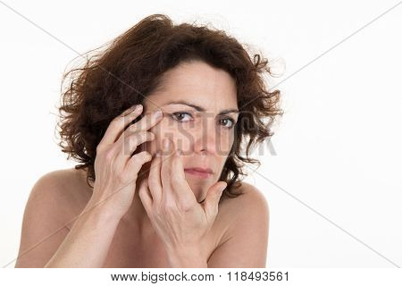 Worried Brunette Woman Pointing Her Eyes With Her Fingers On White Background