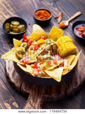 Nachos with melted cheese sauce, salsa and corn cobs in bowl on brown wooden background