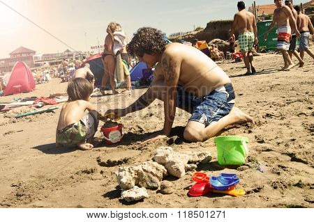 Father helping son with sand castles