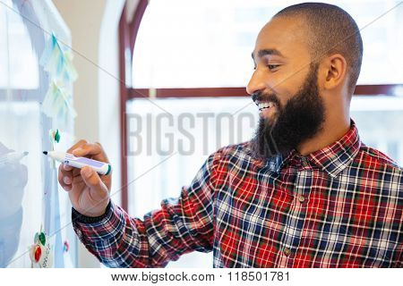 Happy afro american businessman writing something on whiteboard in office