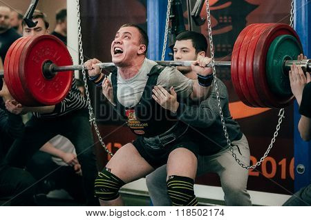 athlete of powerlifter squats barbell