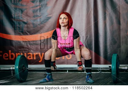 young female athlete performs deadlift barbell