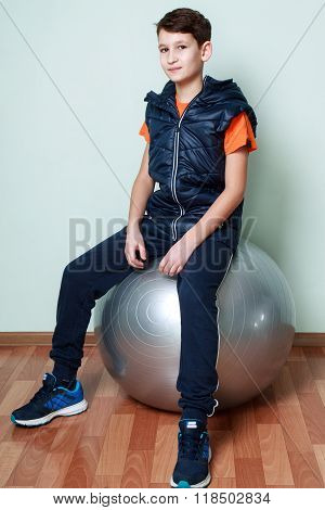 Boy Teenager Sitting On Fitball. Fitness Child In Sportswear.