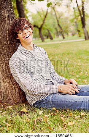 Young hispanic man wearing black glasses, checkered shirt and blue jeans sitting on grass under tree in autumn park, holding notebook and pen in his hands and laughing out loud - laughter concept