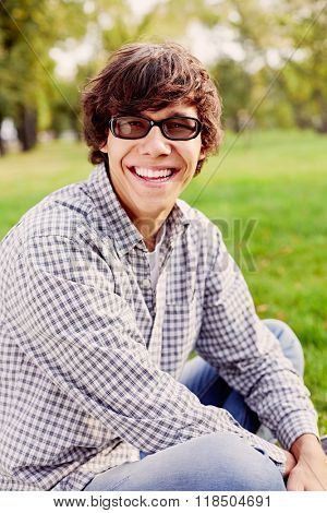 Young hispanic man wearing black glasses, checkered shirt and blue jeans sitting on grass and laughing in autumn park outdoors - laughter concept