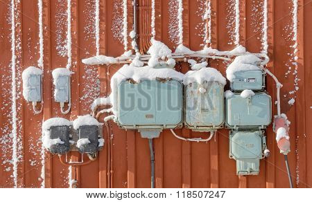 Electric Junction Boxes With Snow, Retro Style On Red Wall