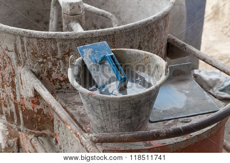 Trowel In Cement Bucket On Concrete Mixer Machine