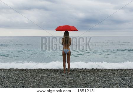 Girl On Beach With Red Umbrella In Front Of A Stormy Sky