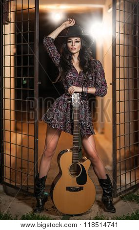 Attractive woman with country look, indoors shot, american country style. Girl with black cowboy hat