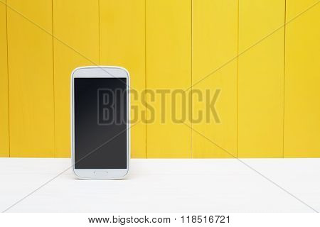 Smart Phone On Yellow Wooden Background
