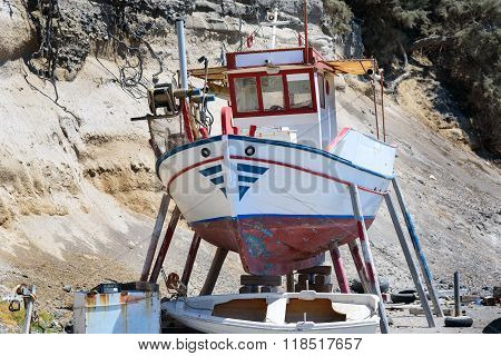 A small fishing boat out of the water, for repairs, in Vlychada village, Santorini island, Greece