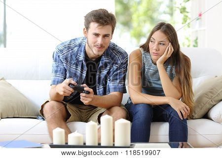 Man Playing Video Games And Girlfriend Bored Beside