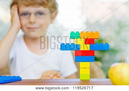 Happy little kid with glasses playing with lots of colorful plastic blocks indoor. child boy having fun with building and creating. Selective focus on multicolored toy