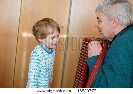 Happy blond little kid boy and his grandfather playing together with accordion. Senior man teaching his grandson cute toddler to play with music instrument at home.