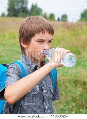 Boy drinking still water from pet bottle outdoors