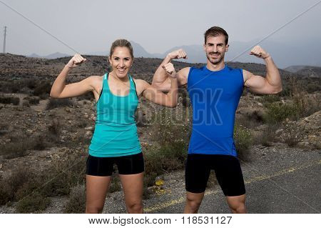 Young Sport Couple Posing And Showing Arms Biceps Muscles Smiling Happy