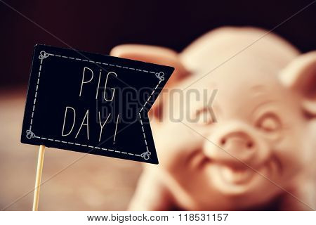 a black flag-shaped signboard with the text pig day and a pig in the background