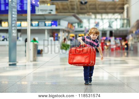 Cute little tired kid boy at the airport traveling. Upset child waiting with big suitcase. Canceled flight due to pilot strike.