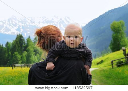 Baby and mother with the Alps mountains in nature