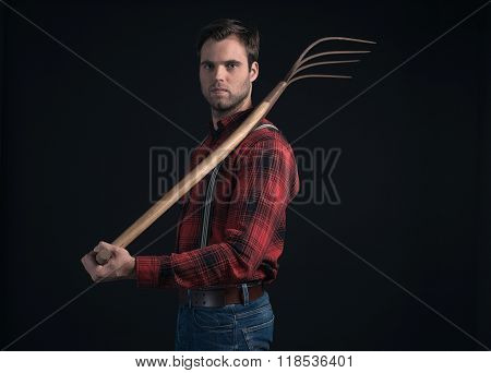 Farmer In Red Checkered Shirt And Suspenders Holding Pitchfork.