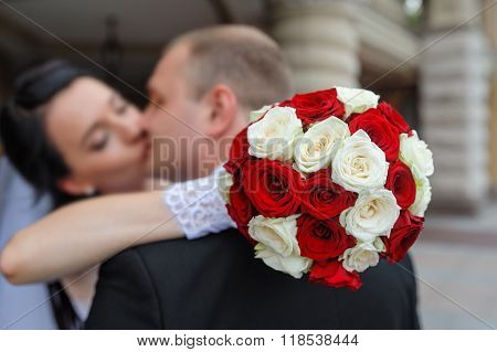 Bride And Groom Kissing In Front Of A Bouquet Of White And Red Roses