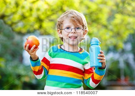 Funny school kid boy with books, apple and drink bottle
