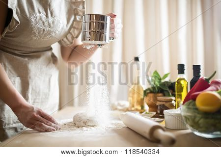 Woman preparing dough basis.Ingredients for baking.Female hands spilling powder on dough