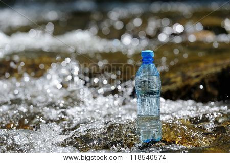 Bottle Pure Water On The Stones In The River.