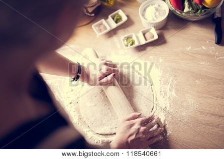 Carbohydrates.Whole grains.Dieting.Cooking food at home.Woman preparing dough on wooden table