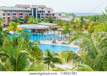 inviting wide open view of Cuban resort in tropical garden with people relaxing near the the swimmi