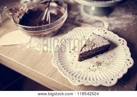 Dark chocolate cake with icing powdered sugar on top served on a cute little vintage ceramic plate