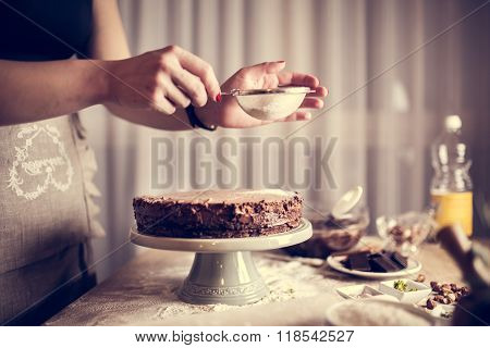 House wife wearing apron making finishing touches on birthday dessert chocolate cake
