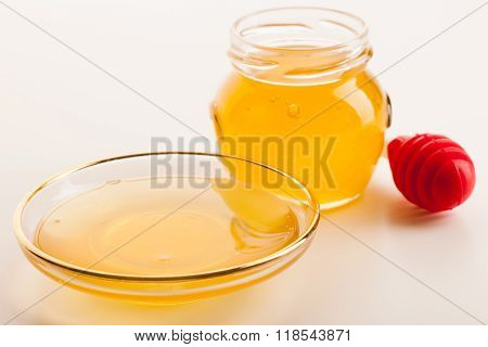 Sweet Sticky Golden Fluid On Transparent Plate Next To Glass Jar Filled With Honey And Red Stick.