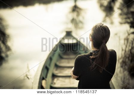 Girl at the old fishing boat looking to the lake.Melancholia sadness sorrow concept