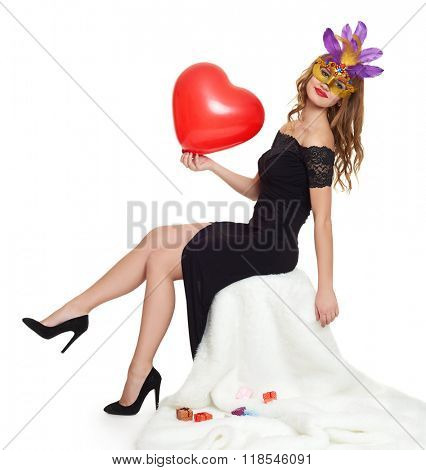 Young woman in black evening gown and carnival mask. Sit on white fur. Heart shaped balloon in hand. Valentine concept.