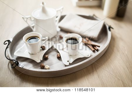 Cups of coffee on rustic wooden table.Two glass cups of coffee on slate tray