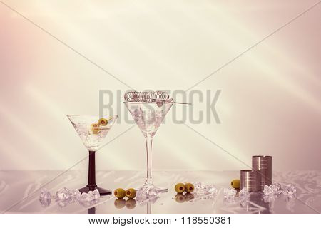 Mixing Martini cocktails over ice  in Art Deco glasses with olives