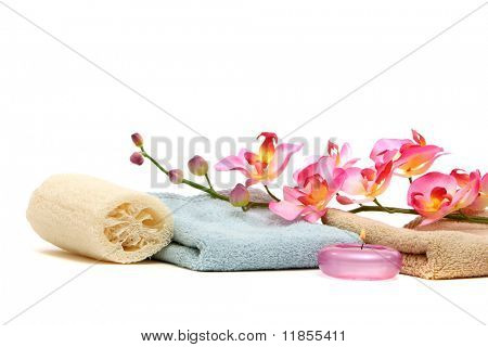 Spa towels, loofah, candle and pink orchid