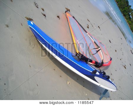 Single Blue Windsurf Board Lying On The Beach At Bintan, Indonesia