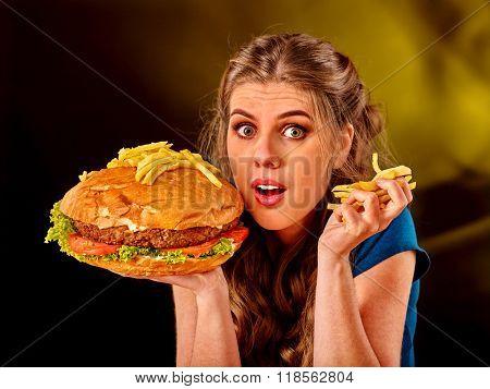 Girl keeps big hamburger. Fastfood concept. Cheeseburger on foreground.