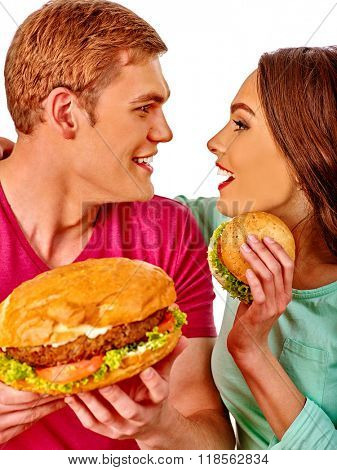 Young loving couple man and woman look in eye each other and eating hamburgers  . Fastfood concept.  Isolated.