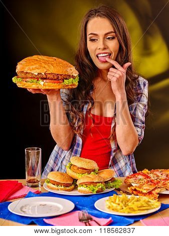 Girl eat fastfood with very big hamburger.