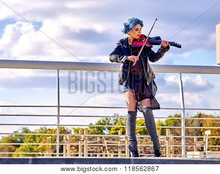 Music street performers girl violinist with blue hair playing  aganist sky with clouds outdoor. Freedom concept.