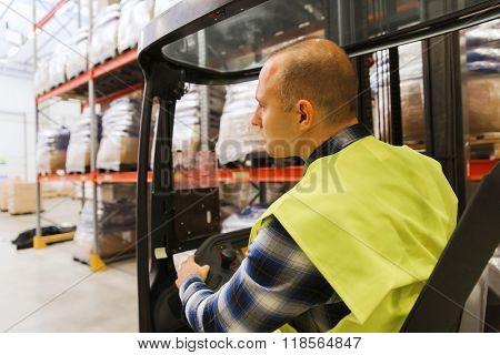 wholesale, logistic, loading, shipment and people concept - man or loader operating forklift loader at warehouse