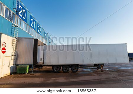 logistic, storage, shipment, transportation and loading concept - warehouse gate and truck loading