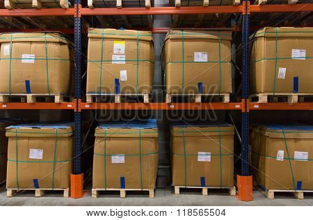 logistic, storage, shipment, industry and manufacturing concept - cargo boxes storing at warehouse shelves